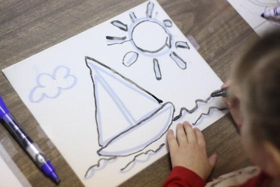 preschooler tracing sailboat on tracing paper