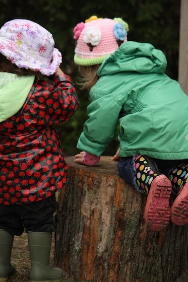 toddlers kneeling on play logs
