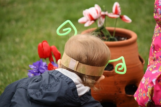 2 year old wearing paper bag band with green pipe cleaner antenae