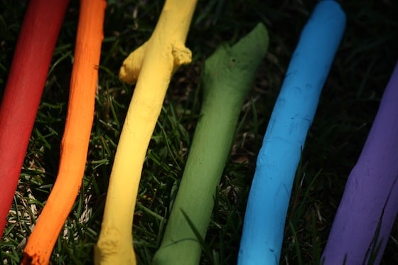 rainbow painted sticks laid out in grass