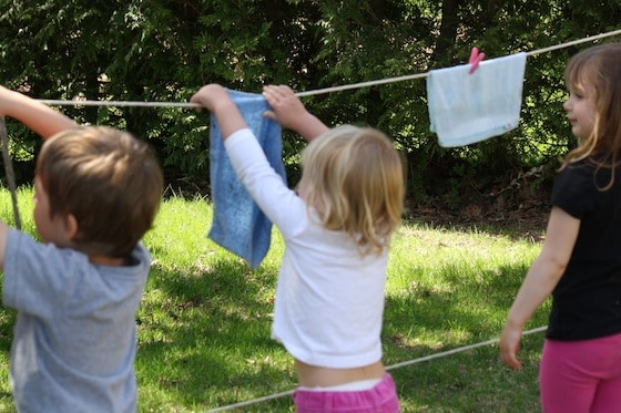 3 preschoolers hanging facecloths on pretend play clothesline