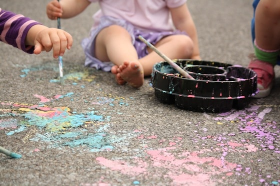 close up toddlers painting with chalk paint in driveway