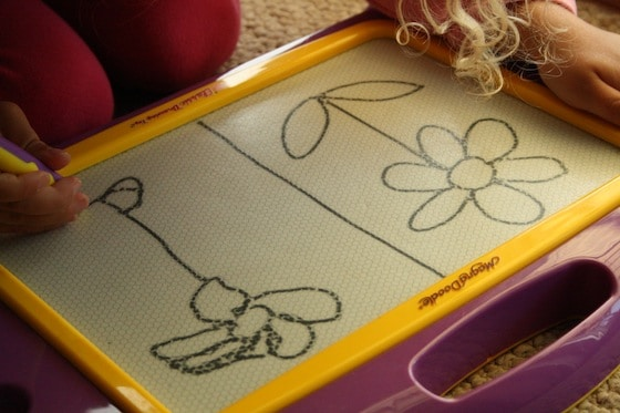 teaching preschooler how to draw a flower on the magna doodle