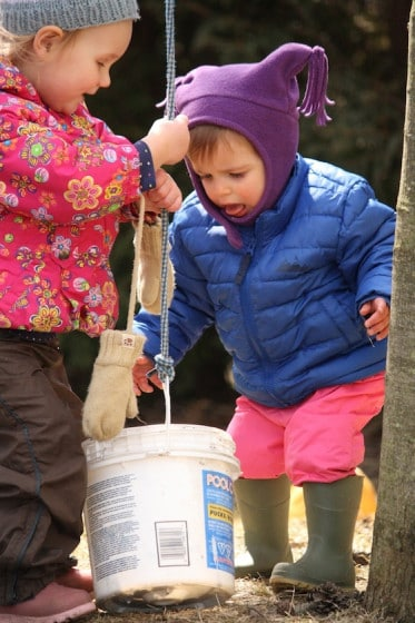 toddlers lifting plastic bucket on rope