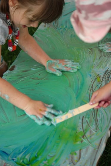 preschooler with both hands in green shaving cream
