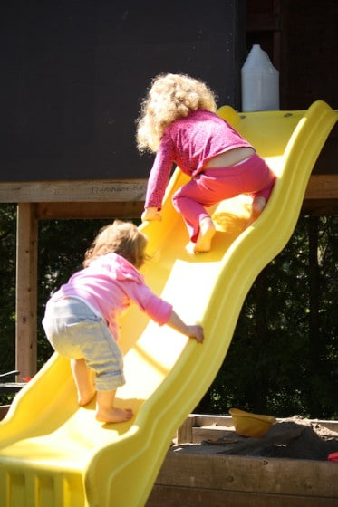 balancing activity - toddler and preschooler climbing up the slide