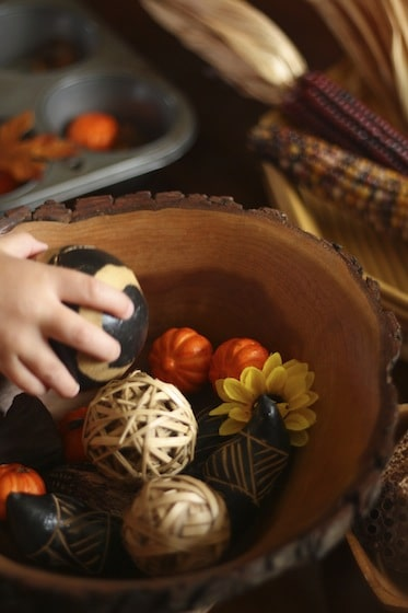 gourds, flowers and decorative balls and bowls on a Fall sensory table