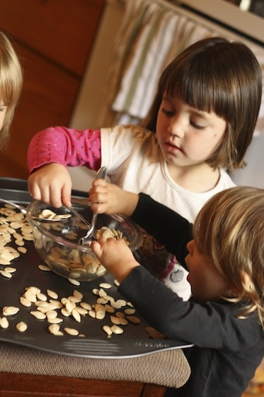 kids tossing pumpkin seeds in olive oil