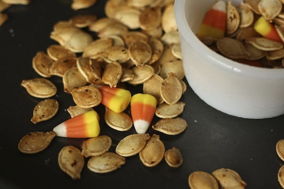 candy corn and roasted pumpkin seeds in bowl on baking sheet