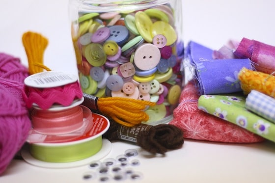 buttons, ribbon, fabric scraps and wool for making homemade paper dolls
