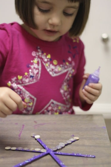 gluing buttons on snowflake ornaments