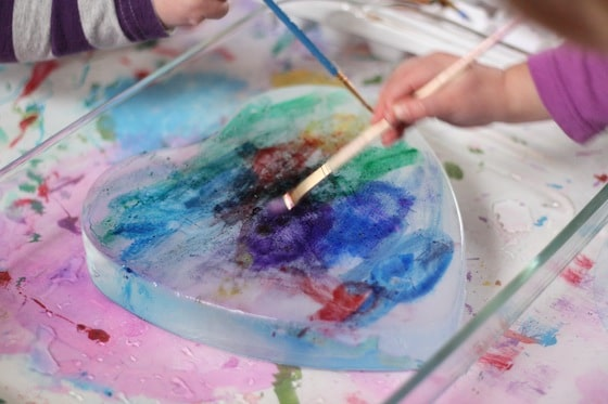 Ice painting activity with a frozen heart and liquid watercolours