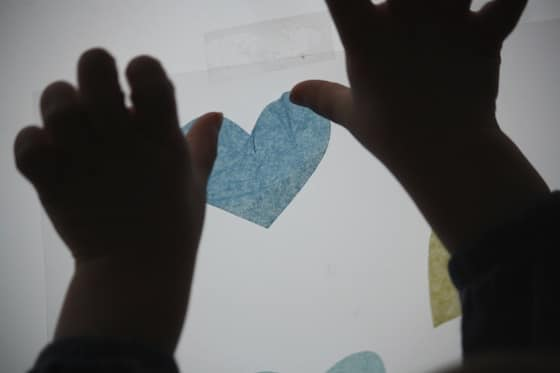 toddler sticking tissue hearts on contact paper window