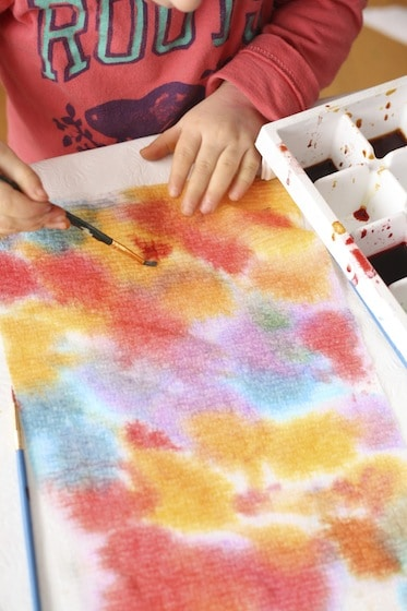 toddler painting paper towel with watercolours