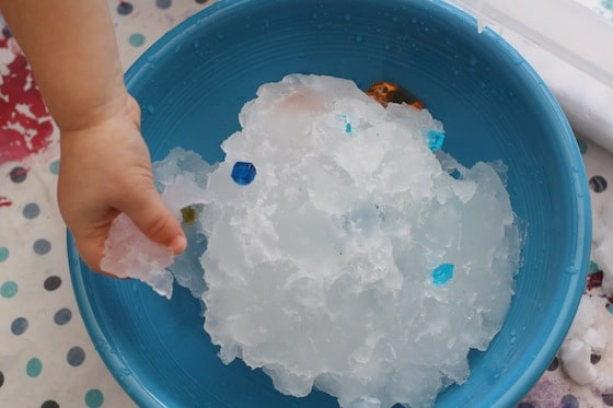 snow turning to slush and ice in a bowl of water