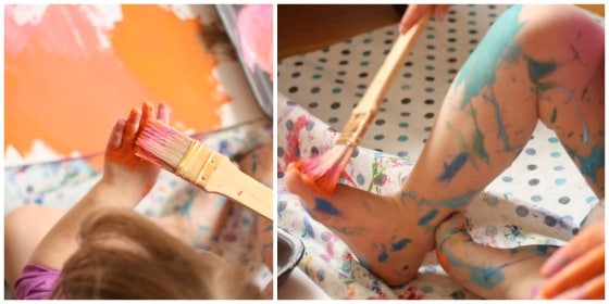 Toddler painting her hands and feet