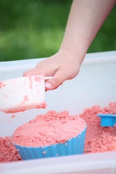 child scooping coloured cloud dough