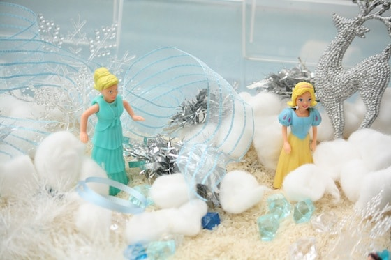 close up rice, cotton balls, anna and elsa figures in plastic bin