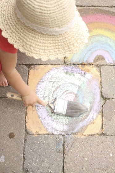 child painting with water over sidewalk chalk drawing