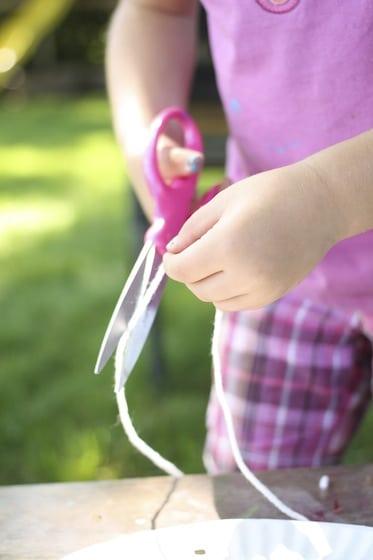child cutting yarn for dream catcher