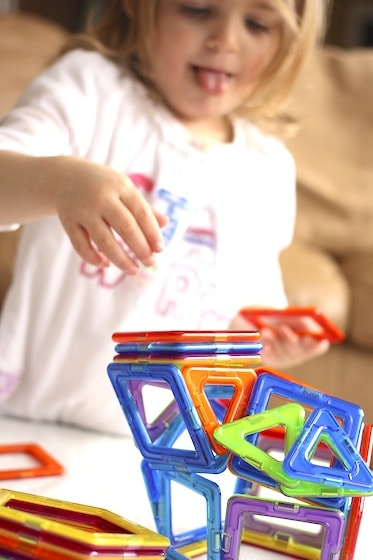 toddler building a 3 dimensional structure with Magformers