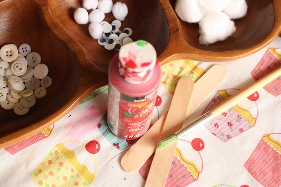 red paint, craft sticks, buttons, cotton balls, google eyes, pom poms