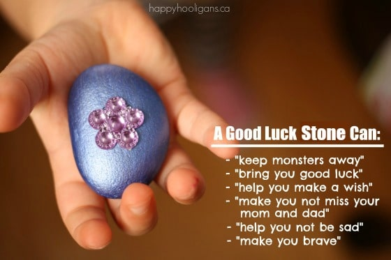 Child's hand holding purple good luck stone with pink flower
