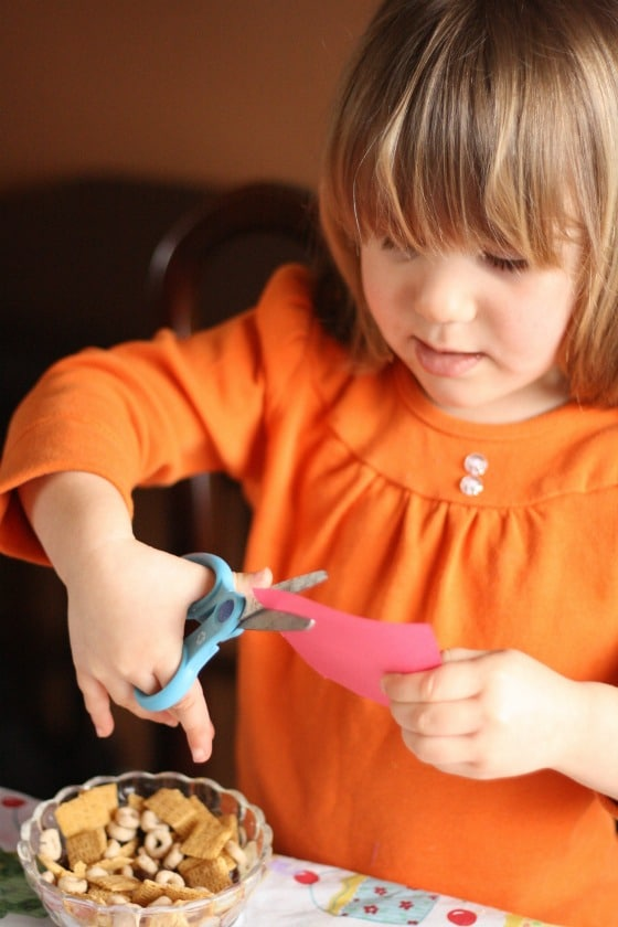 Preschooler cutting paper circles out of card stock