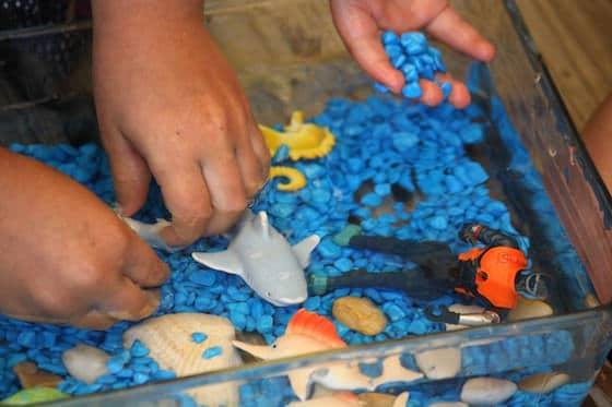 preschooler's hands in miniature ocean sensory bin