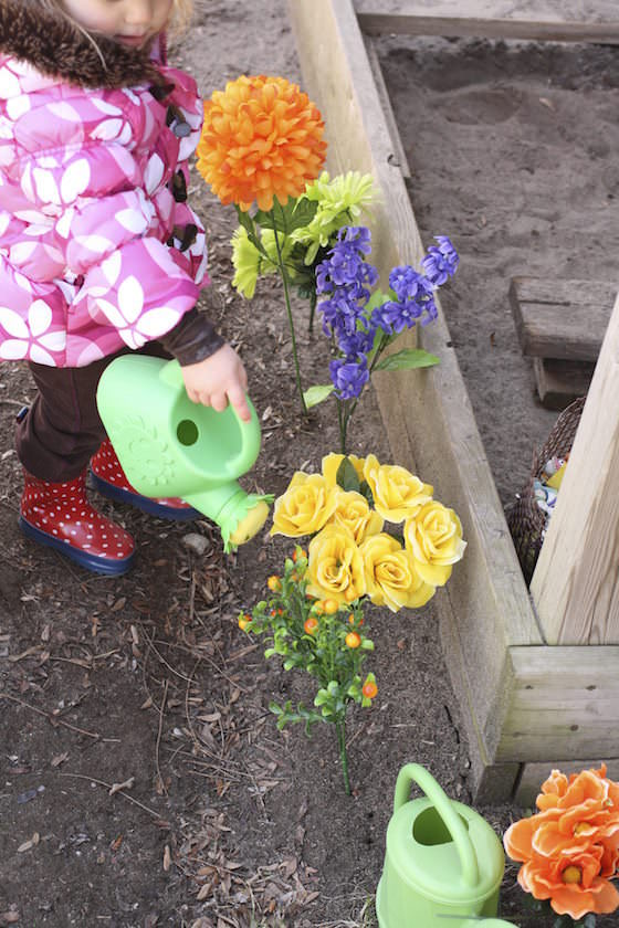 preschooler watering artificial flowers beside sandbox