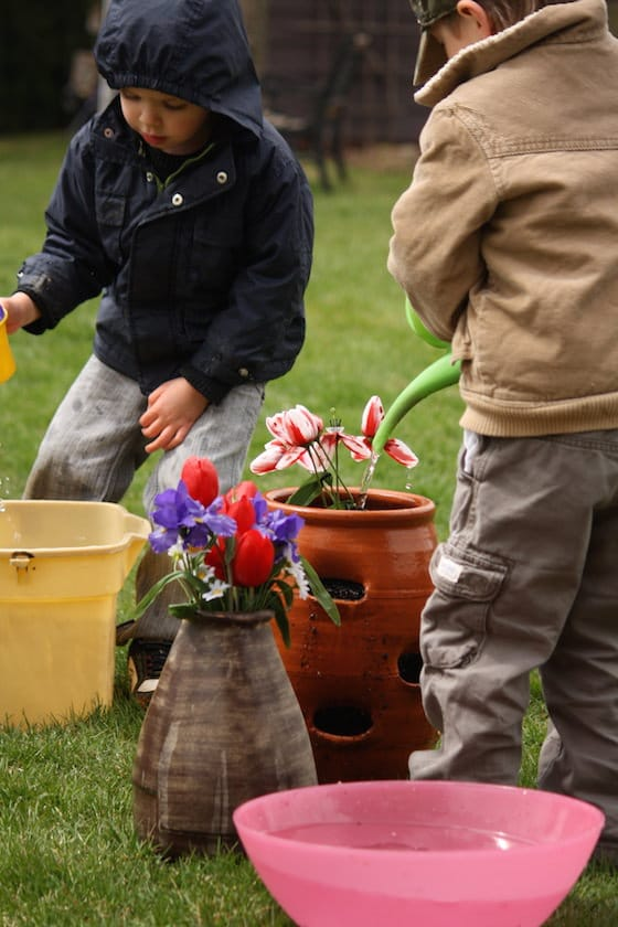 boys water fake flowers in flower pots