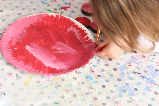 preschooler painting paper plate red
