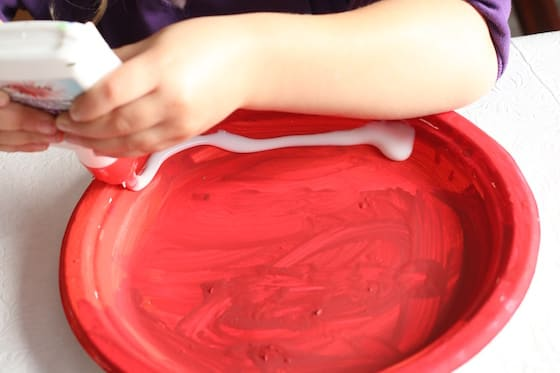 preschooler squeezing glue on red paper plate