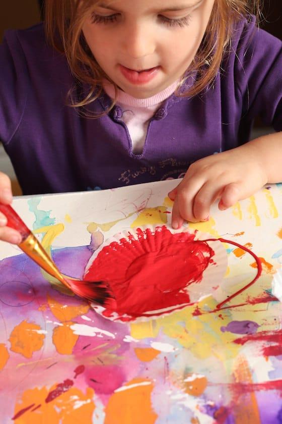 preschooler painting a cupcake liner
