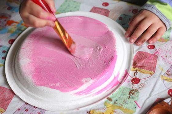 Child painting paper plate with pink paint