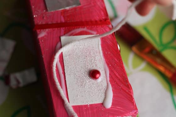 Gluing door on red gingerbread house