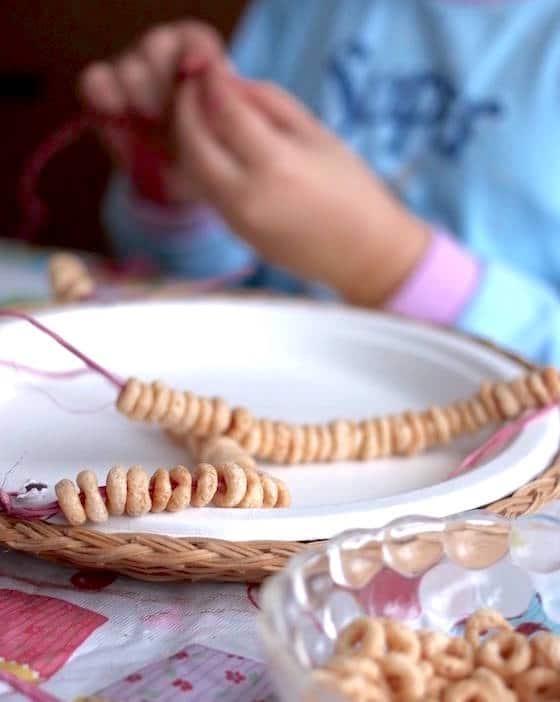 child threading cheerios onto raffia to make homemade bird feeder