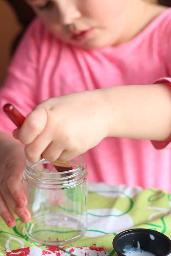 Child brushing glue inside glass jar