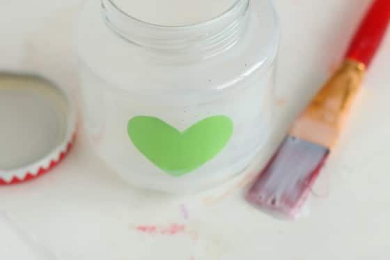 glass jar brushed with glue and contact paper heart stuck inside