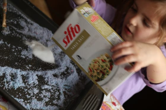 child pouring salt on a baking sheet.