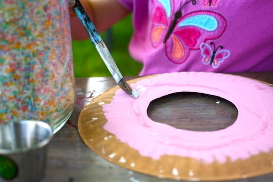 child painting pink icing on a paper plate donut