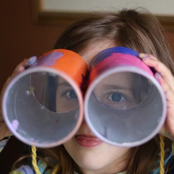 child looking through binoculars she made with pringles cans