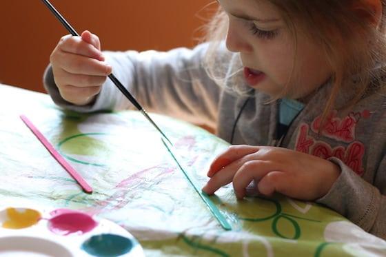 little girl painting wooden stir stick