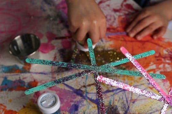 child adding glitter to painted stir sticks
