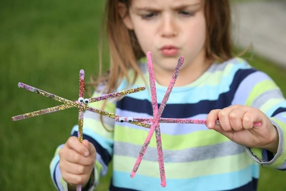 child playing with 2 dragonflies made from wooden stir sticks