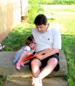 Daddy reading to little girl