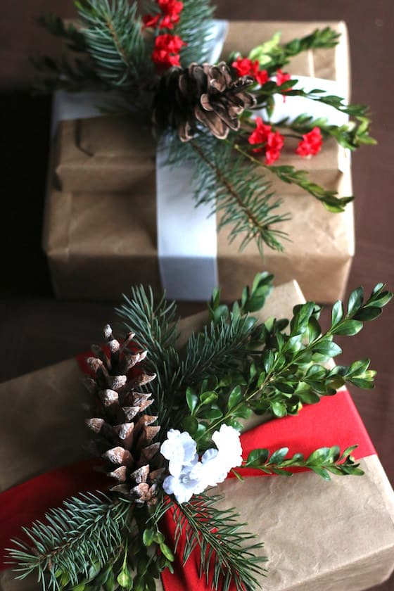 gifts wrapped in brown paper with white ribbon and sprigs of greenery