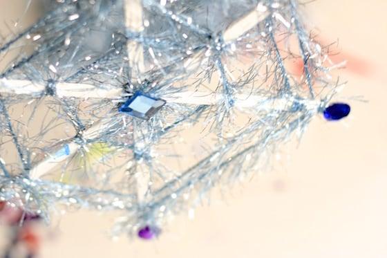 blue yarn snowflake with stir sticks, fuzzy yarn and craft jewels