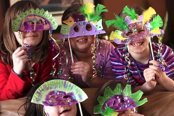 daycare kids holding up homemade mardi gras masks