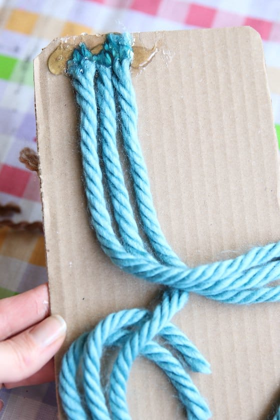 3 strands of blue yarn hot glued to piece of cardboard